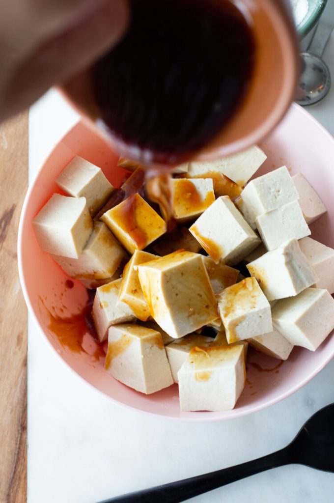 tofu bites in a bowl on a countertop with tamari being poured over the cubes.
