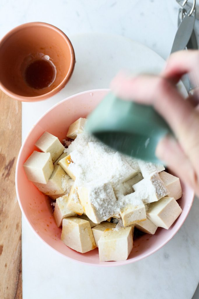 flour being added to a bowl of raw tofu cubes in a bowl on the counter.