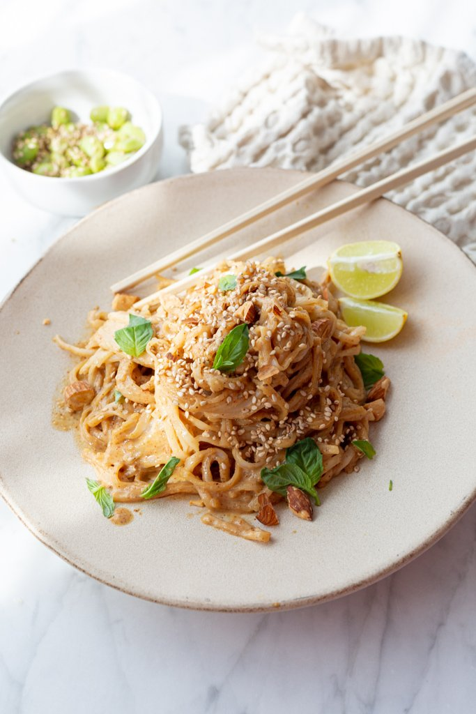 Peanut-free Vegan Pad Thai noodles on a plate on a counter with chop sticks