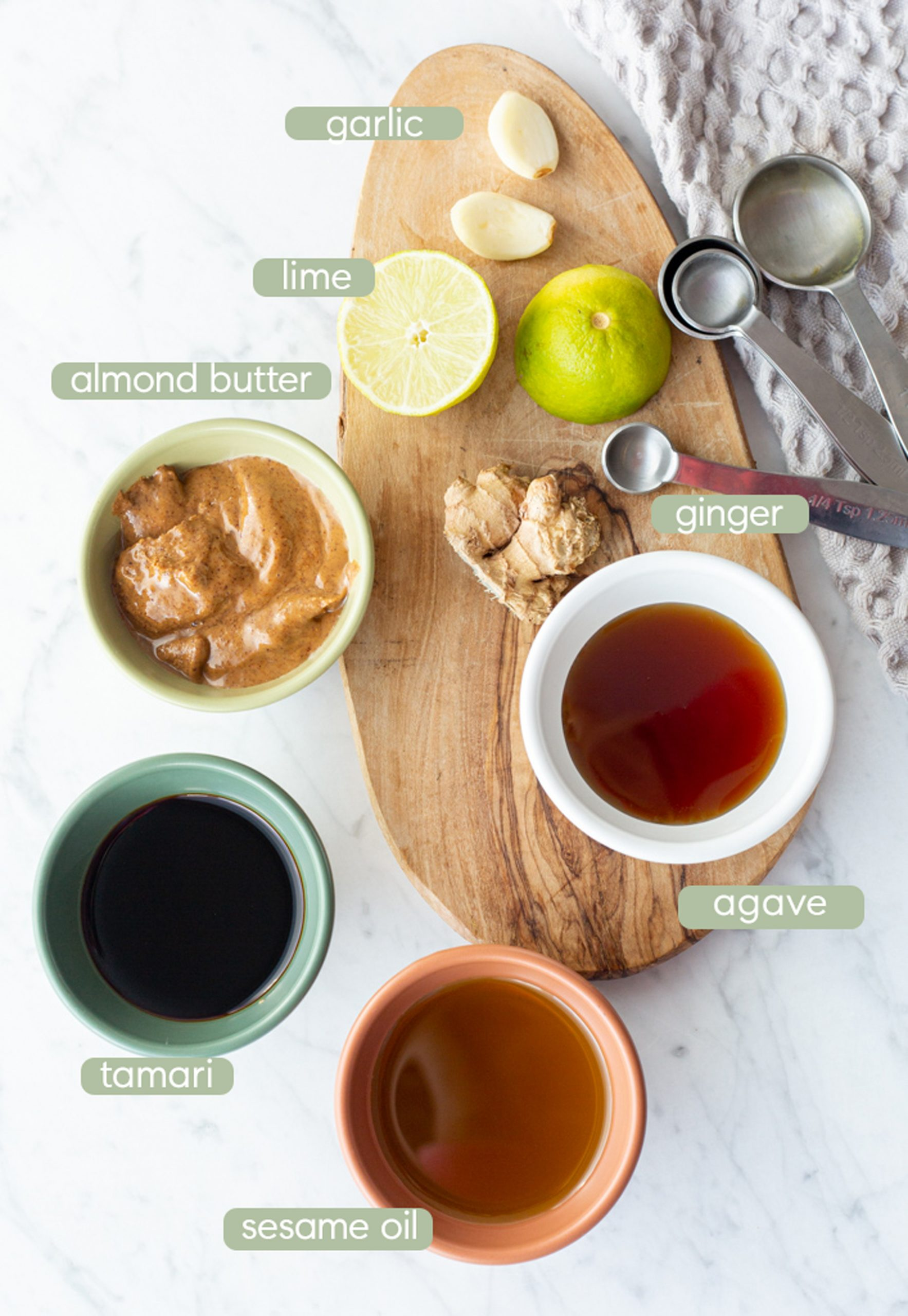 ingredients for thai almond butter dipping sauce in bowls spread on counter