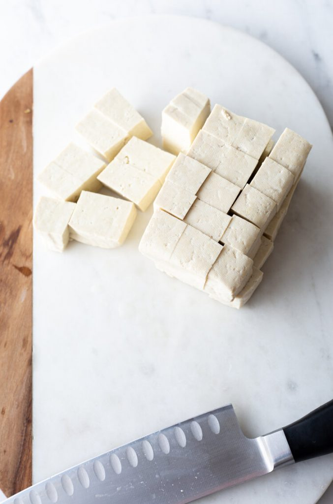 cube of tofu on the countertop cut into small cubes