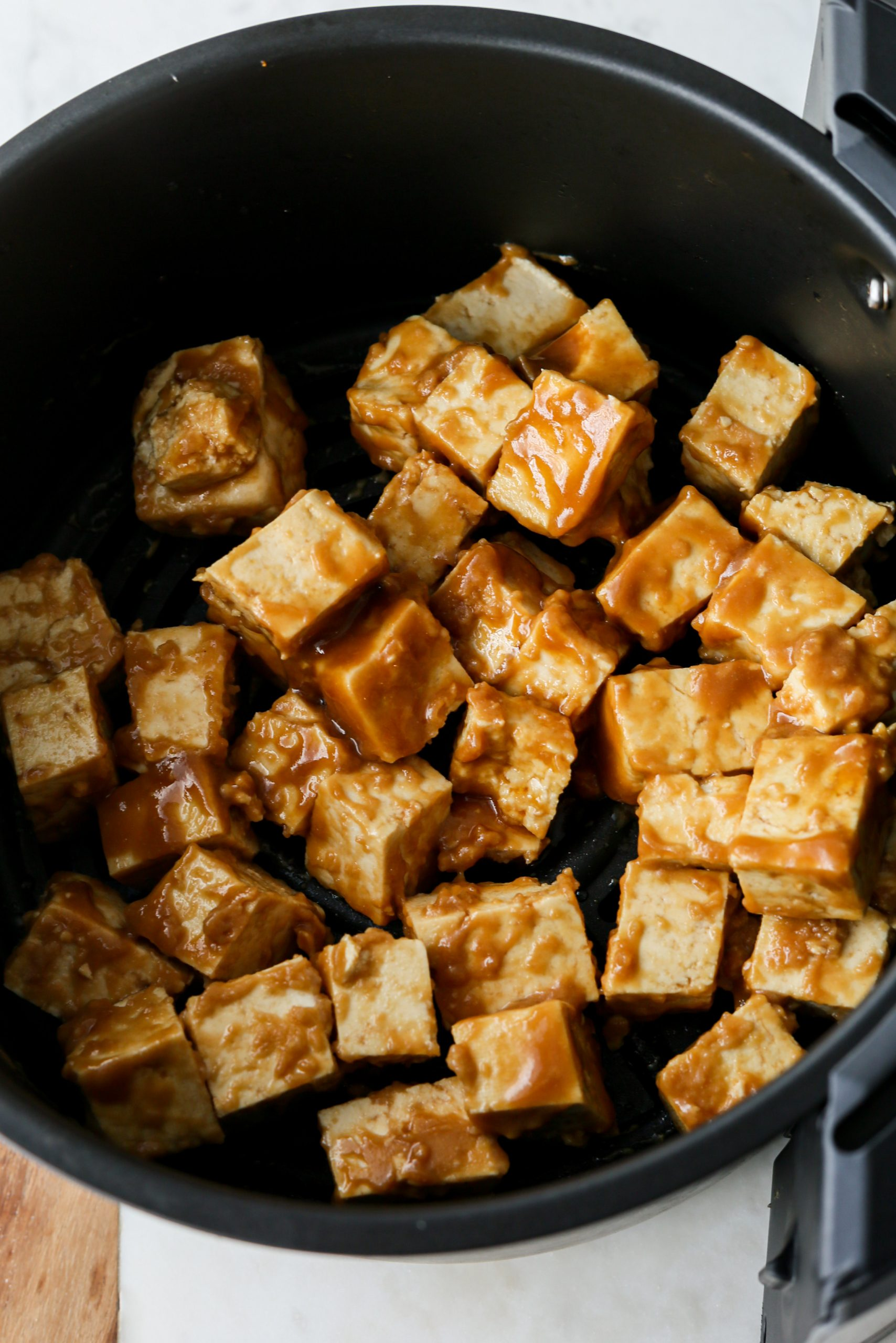 coated cubes of tofu in an air fryer.