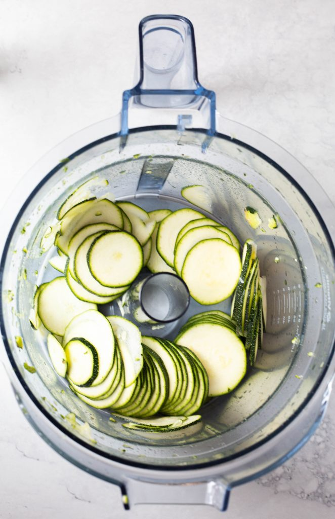 close up of food processor bowl with freshly sliced zucchini