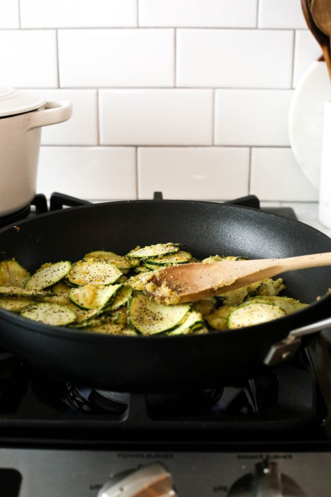 slices of zucchini cooking in frying pan on stove with wooden spoon.