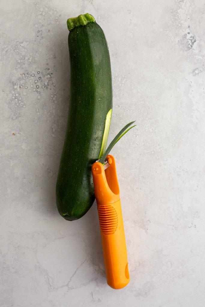julienne peeler peeling a zucchini on a coutertop.