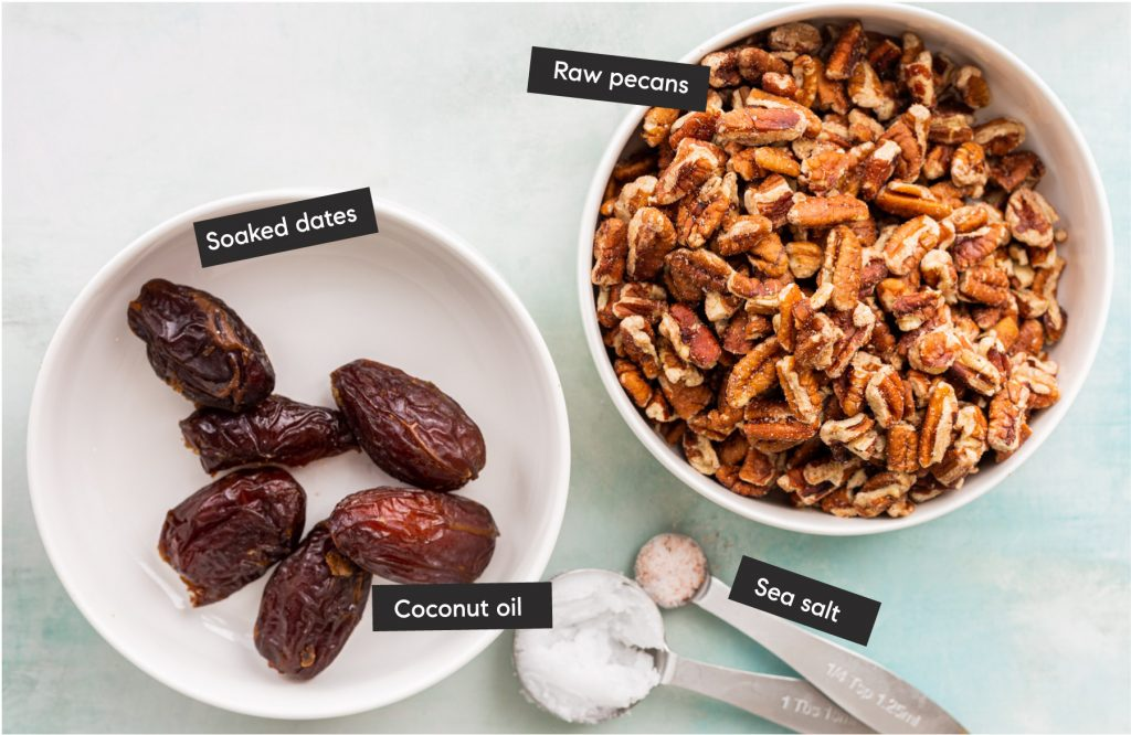 date, pecans, sea salt and coconut oil ingredients spread out on a table in bowls and spoons and labelled.