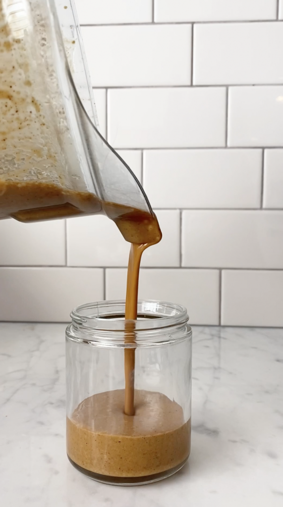 5 minute thai almond butter sauce being poured from blender to a jar