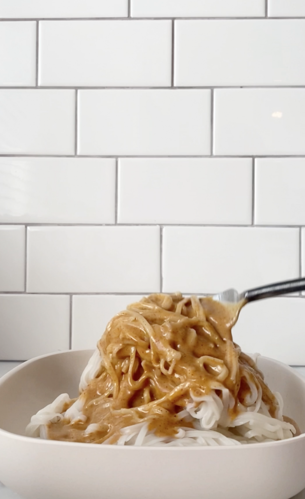 bowl of rice noodles with almond butter sauce poured on it. subway tiles background.